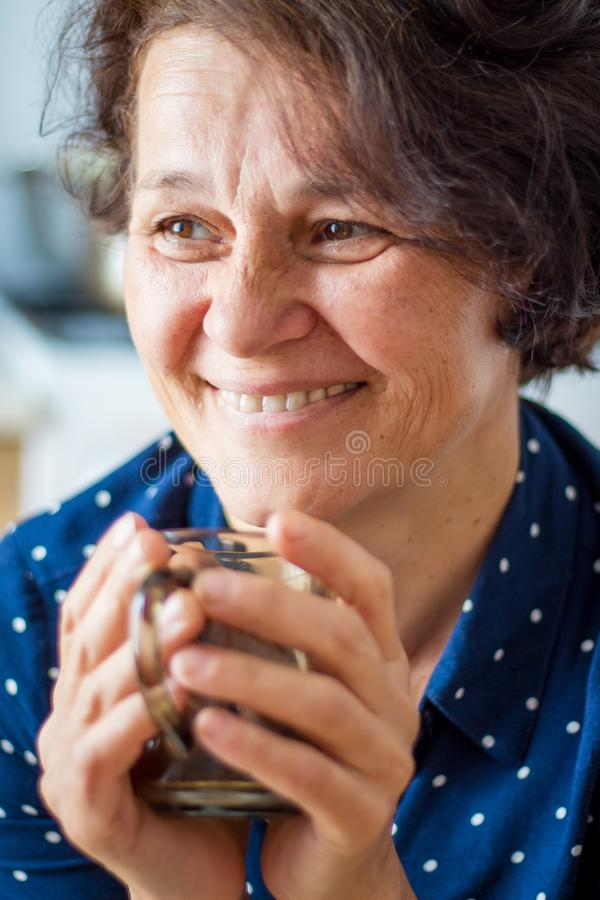 A good stylish middle-aged woman with a cup of coffee. Smiling w. Oman drinks coffee or tea royalty free stock image