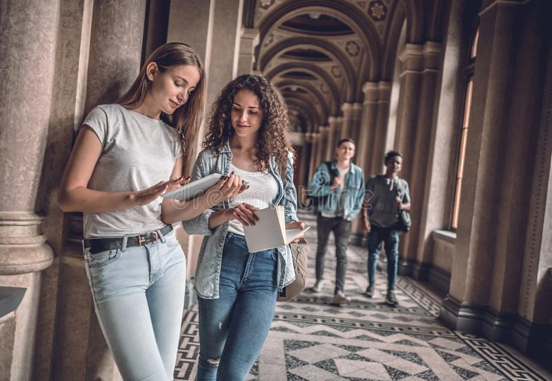 We are good team! Two beautiful students in the university looking at the tablet preparing for exams stock photos