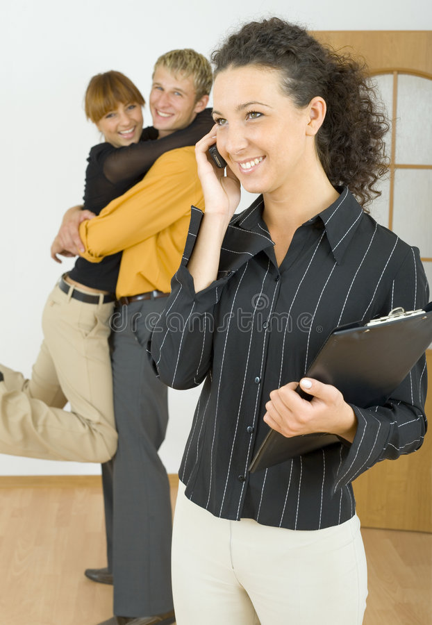 Good transaction. Three people standing in flat. One couple is hugging, other woman is talking by mobile phone. Everyone smiling stock image