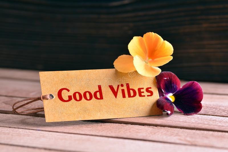 Good vibes tag. Tag banner good vibes and violet flower on wooden desk royalty free stock images