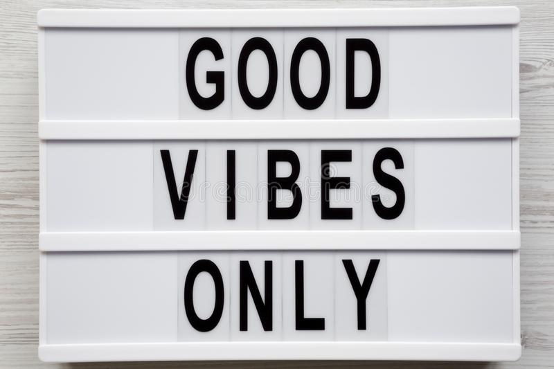 `Good vibes only` words on a modern board on a white wooden surface, top view. From above, overhead, flat lay. Close-up.  royalty free stock image