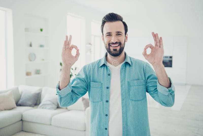 Good-wearing bristle brunet hair man stand in blue casual shirt. Inside bright light house interior with white cosy couch sofa show ok sign on two hands look at royalty free stock images
