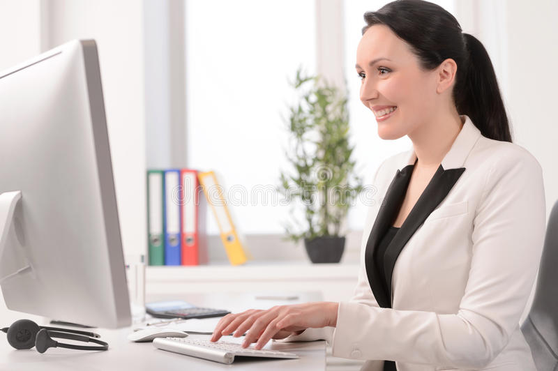 Good working day. Beautiful middle-aged businesswoman sitting at royalty free stock image