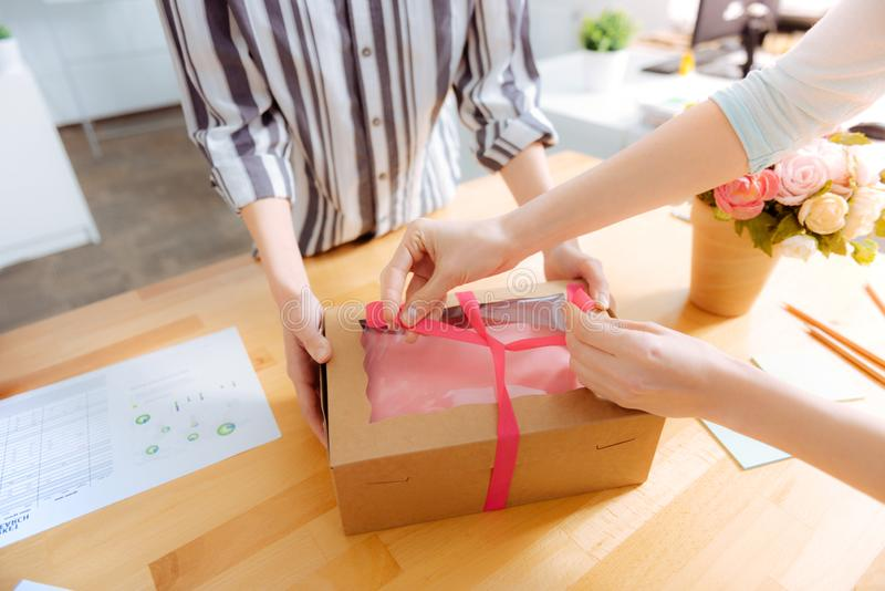 Close up of female hands that tying box in a bow stock photography