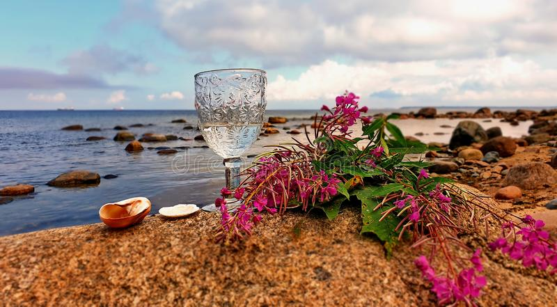 Goodbye Summer Romantic Season Wild tree Autumn leaves and stone on beach sand red Rowanberry and glass of fresh wat. Love Summer Hello Autumn Romantic Season royalty free stock photography