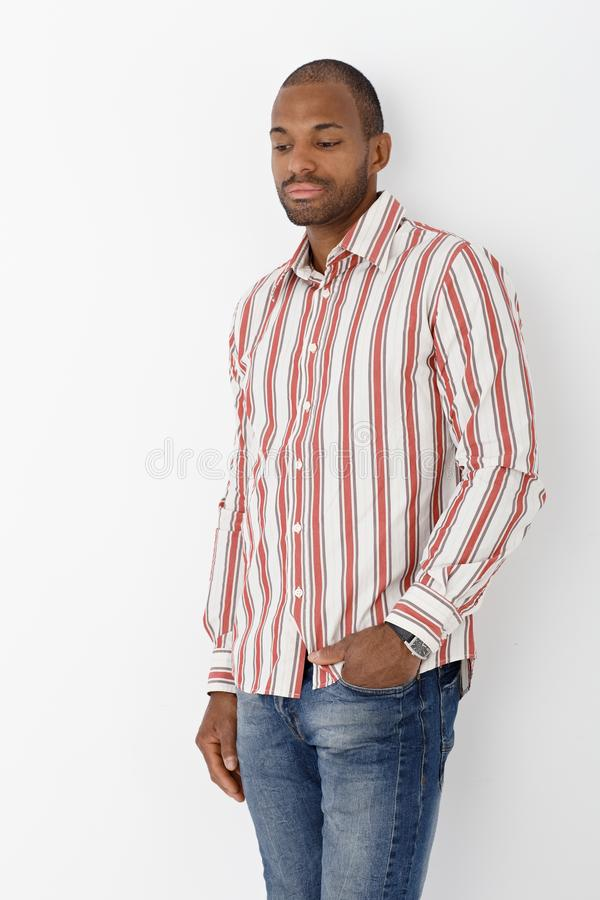 Goodlooking afro man posing. Portrait of goodlooking afro man posing in striped shirt, thinking royalty free stock photography