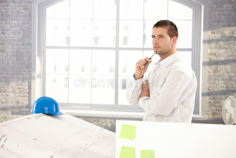 Goodlooking architect making plans royalty free stock image