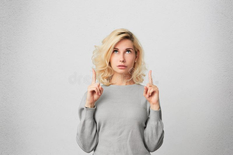Goodlooking blonde female with pierced nose, wears gray sweater looks in amazement as indicates at something upwards. Isolated over white wall stock image