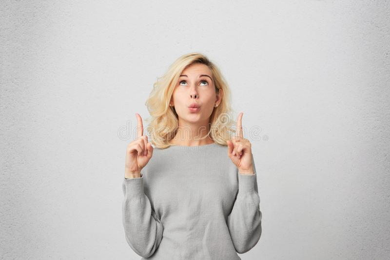 Goodlooking blonde female with pierced nose, wears gray sweater looks in amazement as indicates at something upwards. Isolated over white wall stock photos