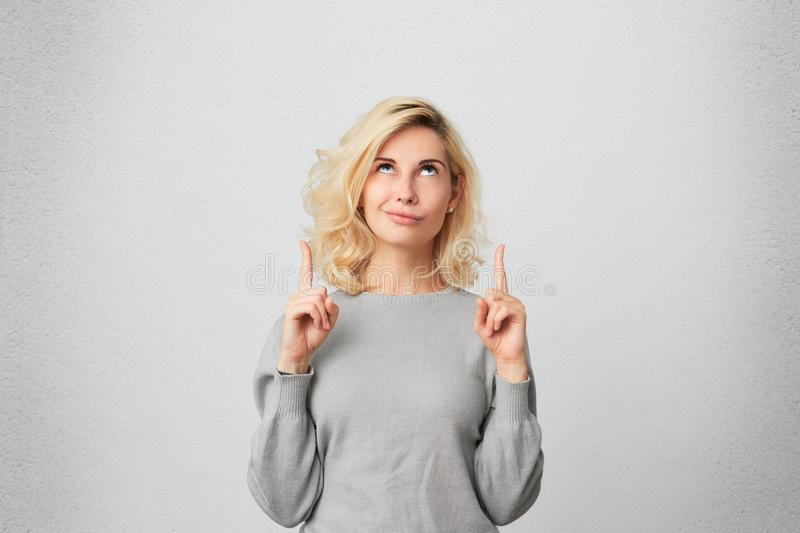 Goodlooking blonde female with pierced nose, wears gray sweater looks in uncertainty as indicates at something upwards. Isolated over white wall stock photos