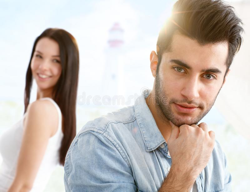 Goodlooking boy and girl. Outdoor portrait of goodlooking boy, girl at background looking back, flirting royalty free stock photos