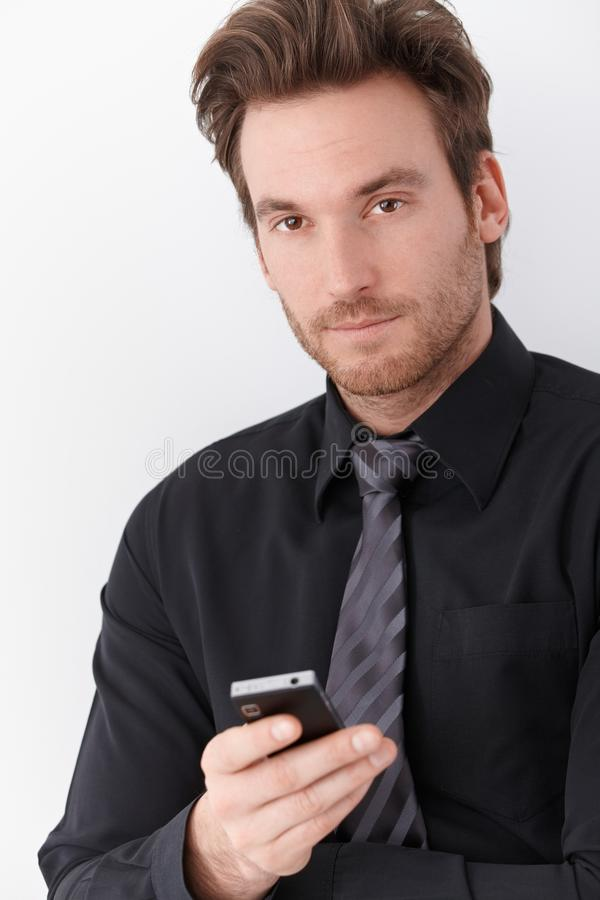 Goodlooking businessman holding mobile phone. Goodlooking young businessman holding mobile phone royalty free stock image