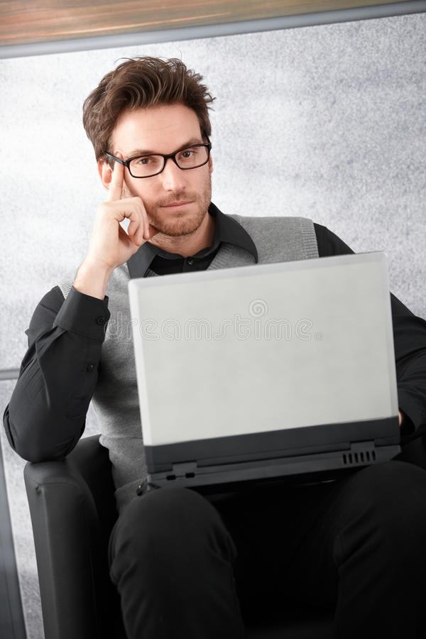 Goodlooking businessman with laptop. Goodlooking businessman sitting in office lobby, working on laptop stock photos