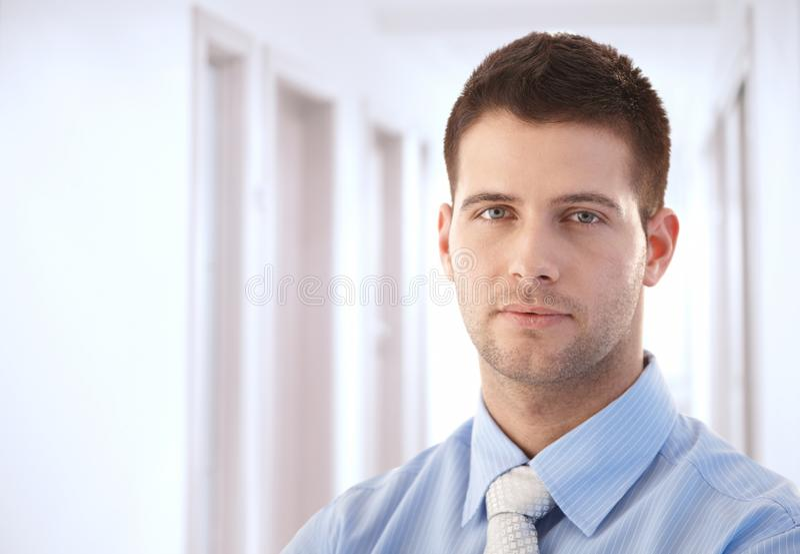 Goodlooking businessman standing in hallway. Goodlooking young businessman standing in hallway royalty free stock images