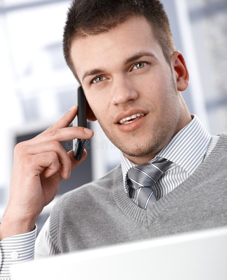 Goodlooking businessman talking on mobile phone. Goodlooking young businessman talking on mobile phone royalty free stock photography