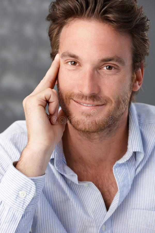 Goodlooking confident male portrait. Man smiling at camera royalty free stock image