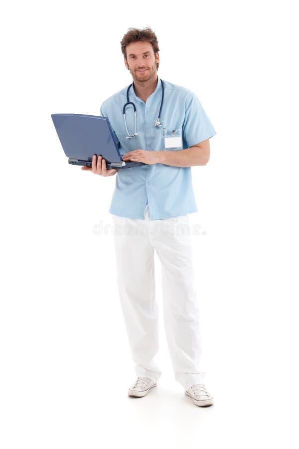 Goodlooking doctor working on laptop smiling. Goodlooking young doctor working on laptop, smiling at camera stock photos