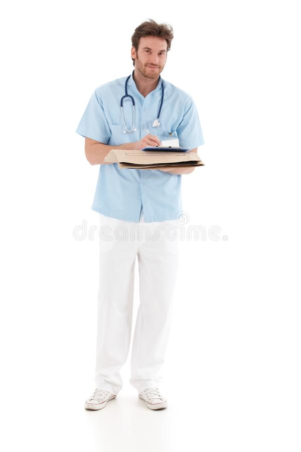 Goodlooking doctor writing notes. Holding papers, standing, smiling royalty free stock photo