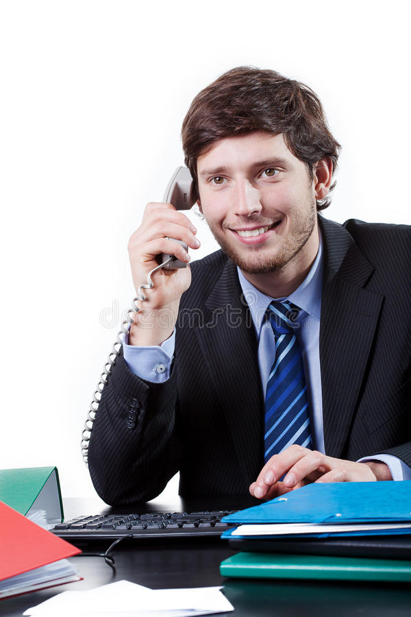 Goodlooking employee at office. Goodlooking employee talking on the phone at office stock image