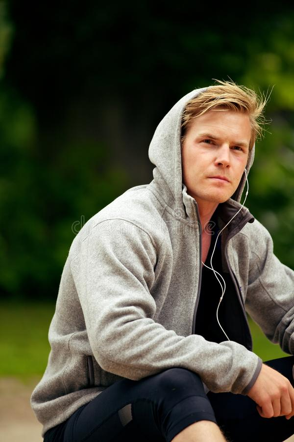 Goodlooking guy sitting alone. At the park listening to music stock images