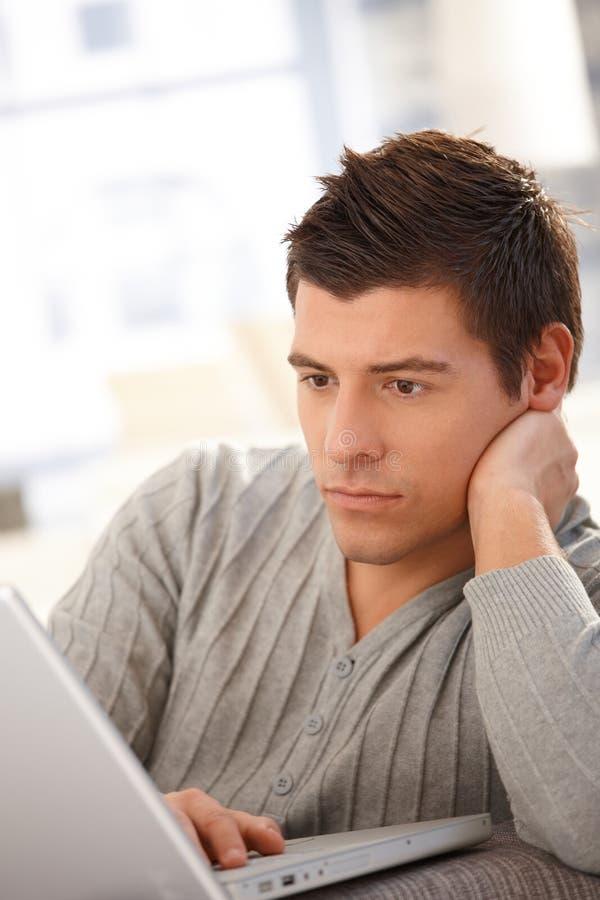 Goodlooking guy using laptop. Computer, looking at screen, thinking royalty free stock photography