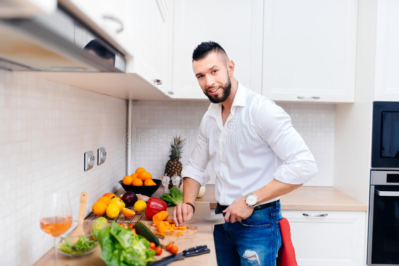 Goodlooking male chef cooking salad in modern kitchen. Details of professional chef using knife and cutting vegetables royalty free stock photos
