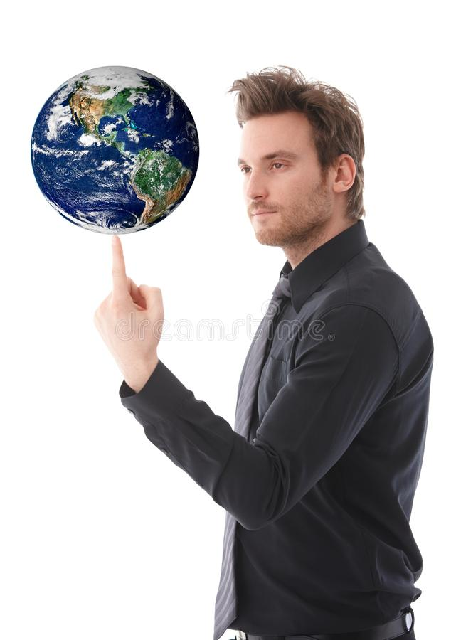 Goodlooking man balancing a globe on forefinger. Goodlooking young businessman balancing a globe on his forefinger, concentrating stock image