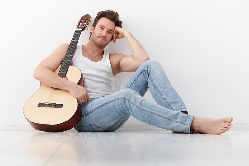 Goodlooking man with guitar smiling. Goodlooking young man sitting by wall, holding guitar, smiling stock images