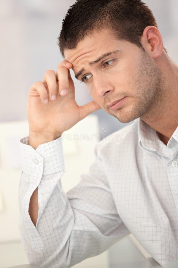 Goodlooking man having headache. Goodlooking businessman having headache in office royalty free stock images