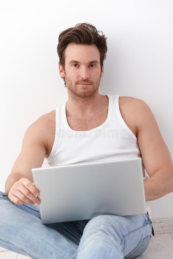 Goodlooking man with laptop. Goodlooking young man using laptop, sitting on floor stock photography