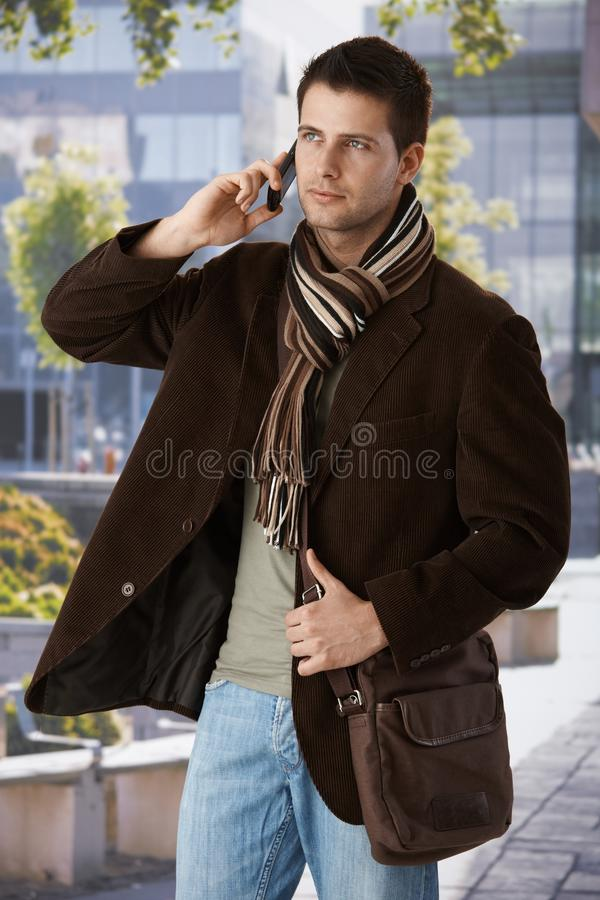 Goodlooking man on phone outdoors. Goodlooking man on mobile phone call standing outside of office building in spring sun, wearing trendy bag and scarf royalty free stock photo
