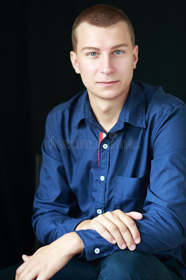 Goodlooking man. Portrait of determined goodlooking man wearing blue shirt, black background royalty free stock images