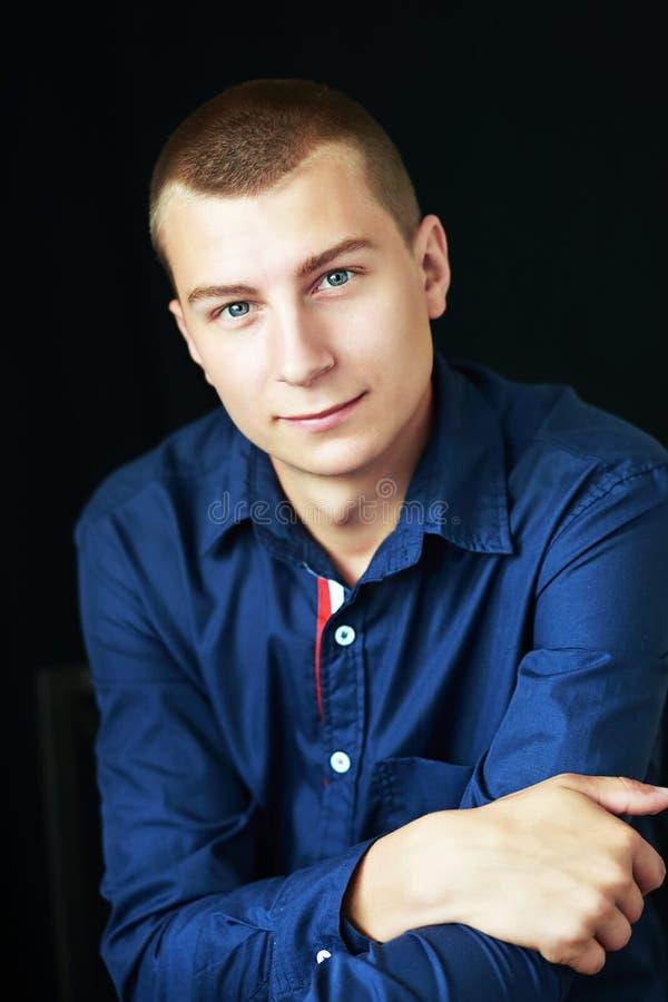 Goodlooking man. Portrait of determined goodlooking man wearing blue shirt, black background stock photography