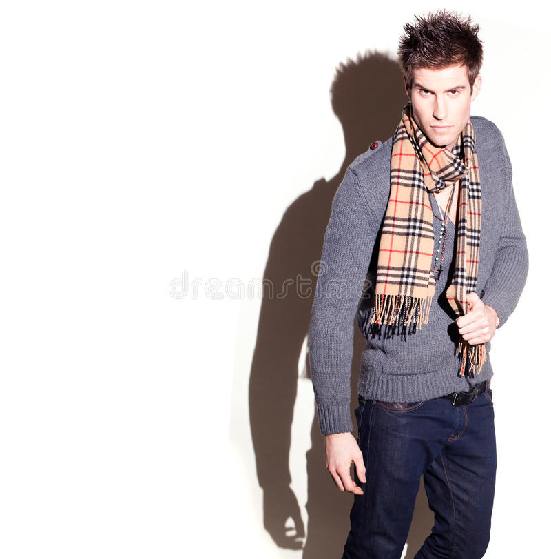 Goodlooking Man In Scarf. Goodlooking tall slim young man with spiky hair wearing a scarf, slightly elevated three quarter studio portrait with defined shadow stock image