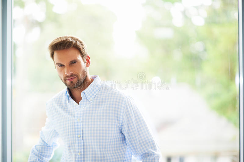 Goodlooking man in shirt standing against the window. Portrait of handsome and happy man stock photo