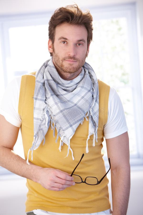 Goodlooking man standing front of window. Goodlooking young man standing front of window at home, wearing vest and scarf stock photography