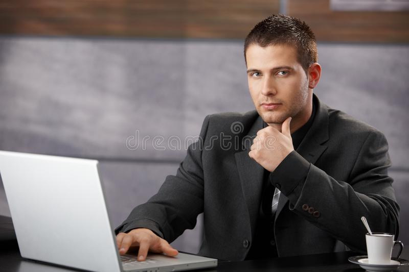 Goodlooking manager sitting at desk in office. Goodlooking manager sitting at desk, using laptop in elegant office stock photography
