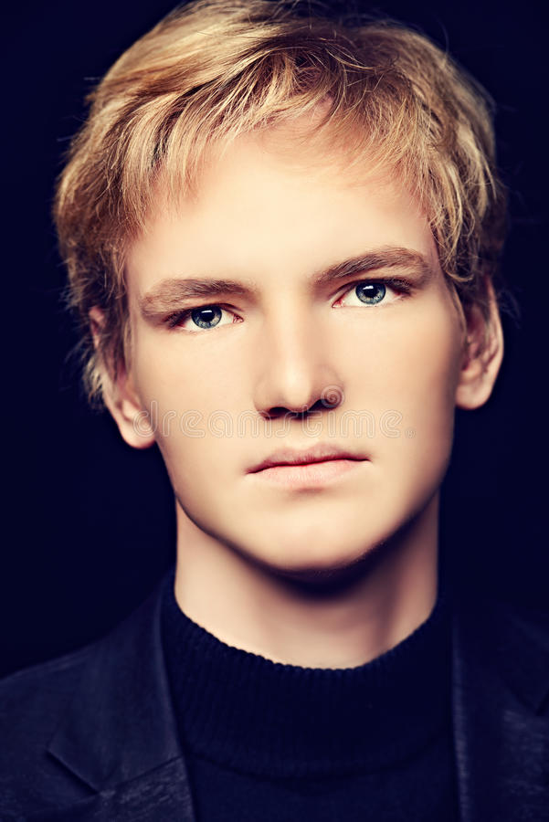Goodlooking. Portrait of a serious handsome young man looking at camera. Black background stock photo