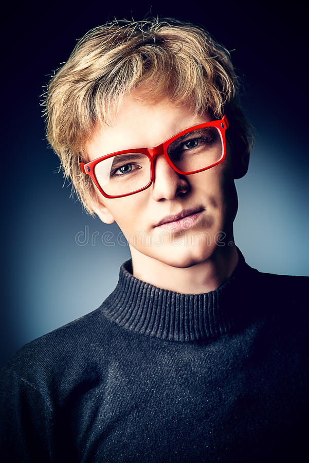 Goodlooking. Portrait of a serious handsome young man in spectacles looking at camera. Black background royalty free stock photography
