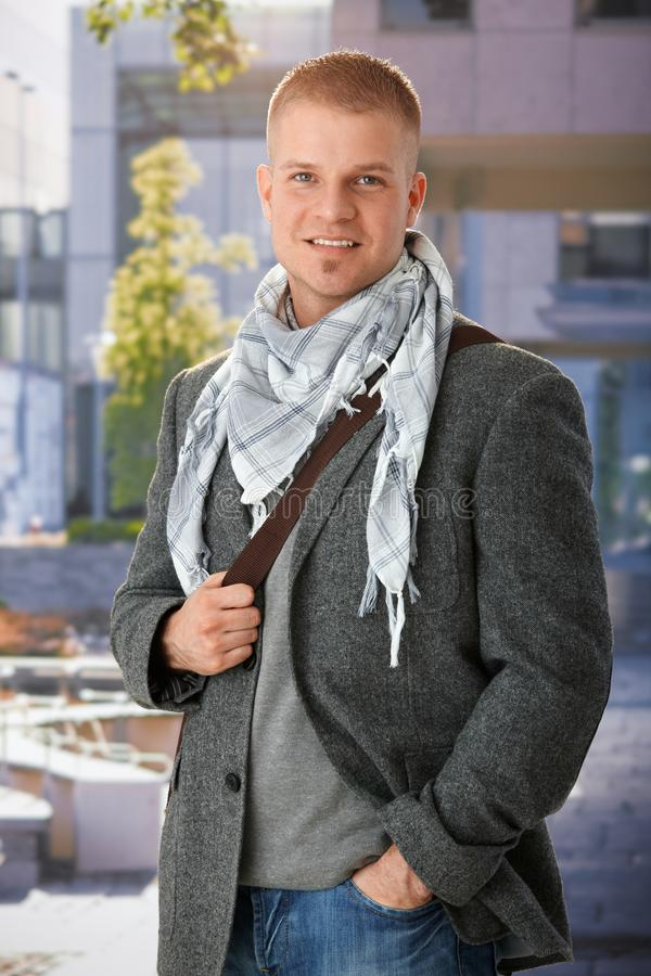 Goodlooking stylish guy. Outdoor portrait of goodlooking stylish guy standing, wearing scarf, smiling at camera stock photography