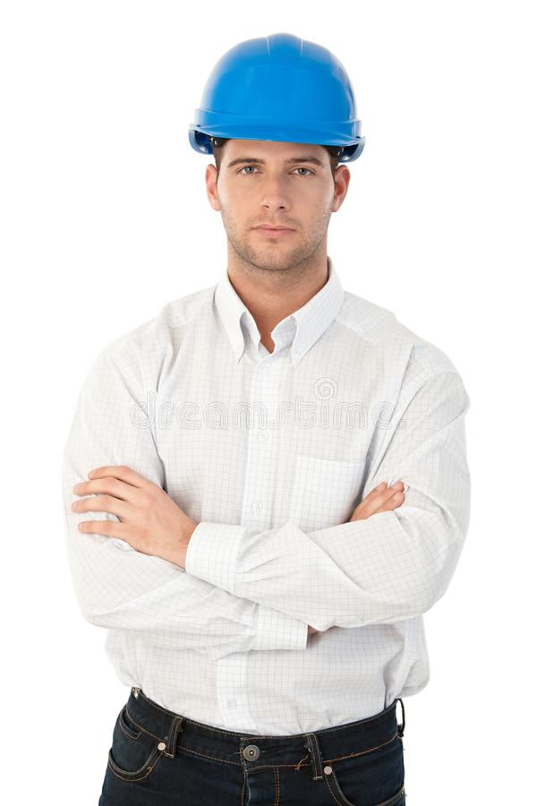 Goodlooking young architect standing arms crossed. Wearing hardhat stock photos