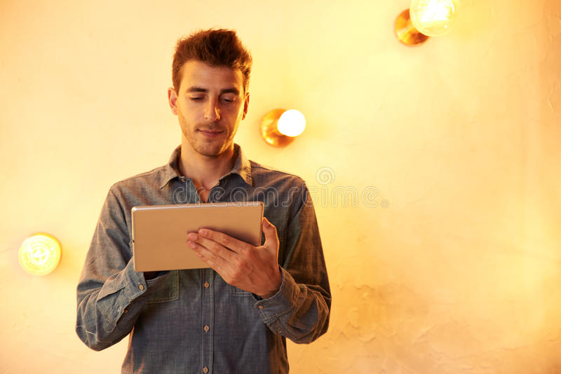Goodlooking young male texting in tablet. Goodlooking young male texting on his tablet with a knowing smile while standing in front of a brightly lit wall stock photo