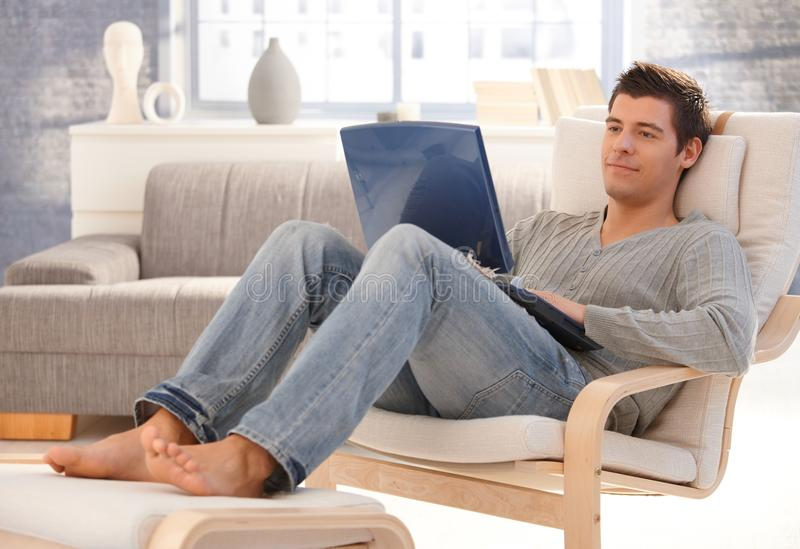 Goodlooking young man relaxing at home with laptop royalty free stock photo