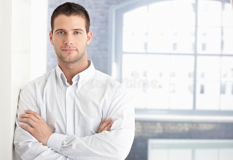Goodlooking young man standing arms crossed.  stock photo