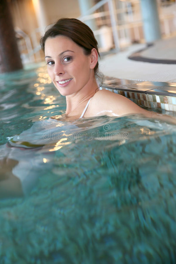 Goodlooking young woman relaxing in the pool. Beautiful woman relaxing in spa swimming-pool stock photos