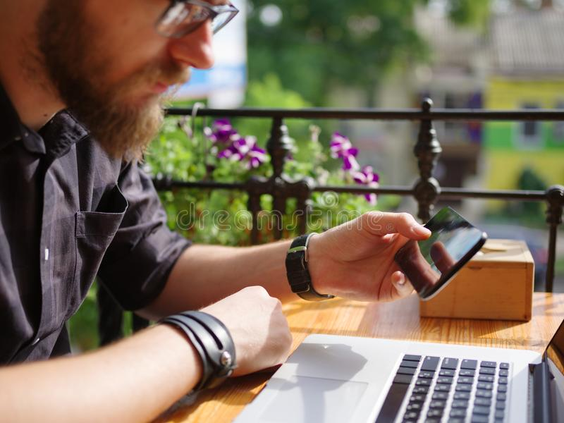 Goodly młody człowiek pracuje na laptopie podczas gdy siedzący outdoors pojęcia prowadzenia domu posiadanie klucza złoty sięgając obrazy stock