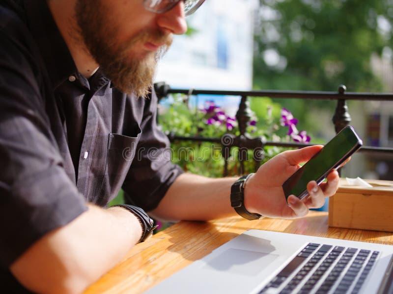 Goodly młody człowiek pracuje na laptopie podczas gdy siedzący outdoors pojęcia prowadzenia domu posiadanie klucza złoty sięgając obrazy royalty free