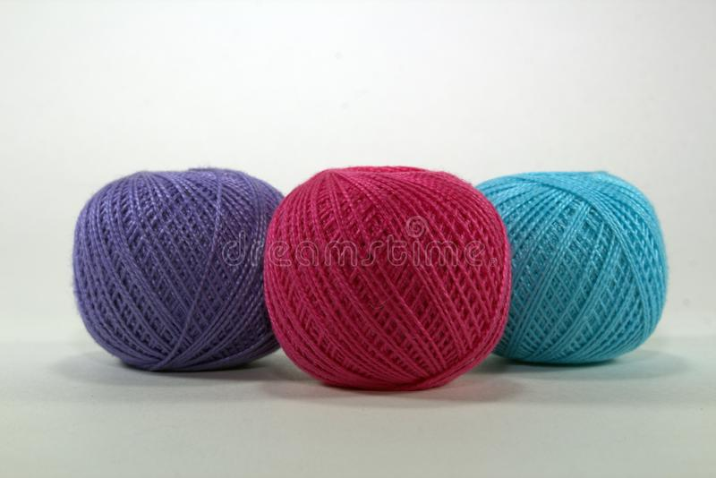 Three clumps of natural cotton, burgundy, blue and purple for needlework on a white background stock images