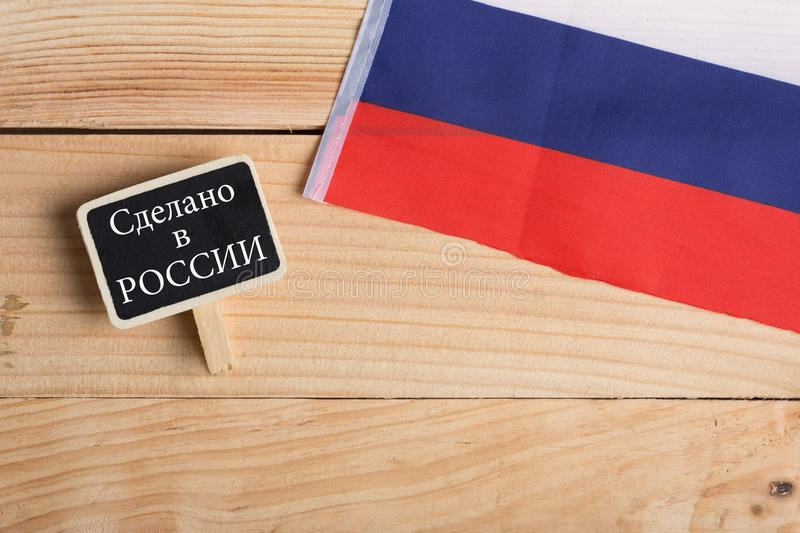 Goods and services concept - russian country& x27;s flag, blackboard with text in russian language Made in Russia. On wooden background, buy, local, label royalty free stock photography
