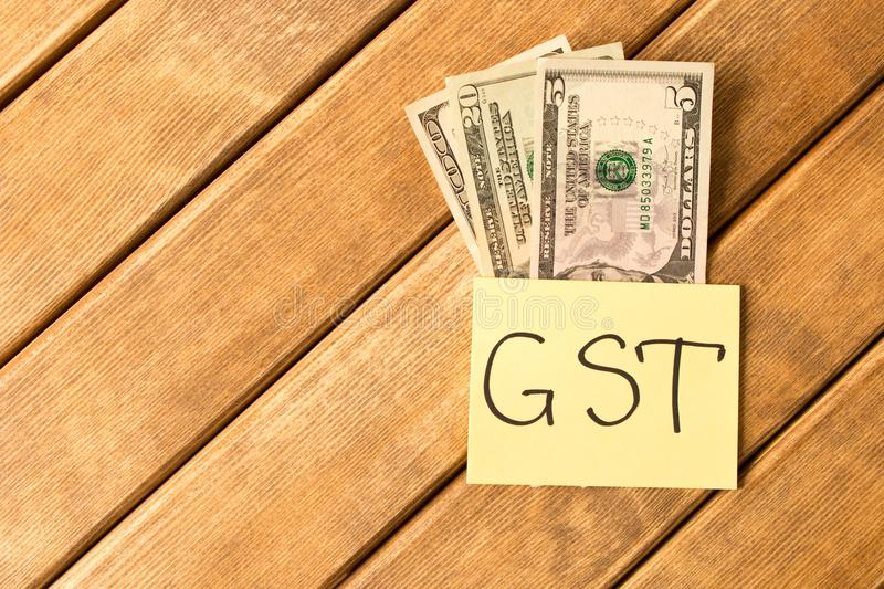 Goods and Services Tax . GST inscription with banknotes on wooden background royalty free stock image
